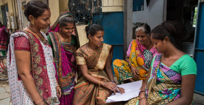 Women in India on laptop computer outside of their home