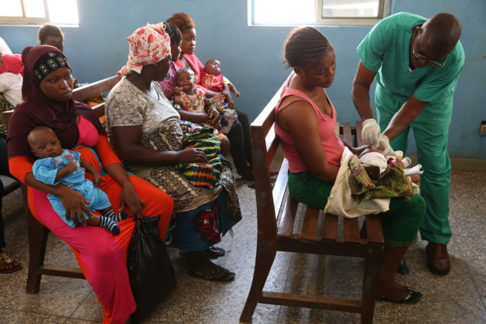 Women holding young children as they wait to get them vaccinated.