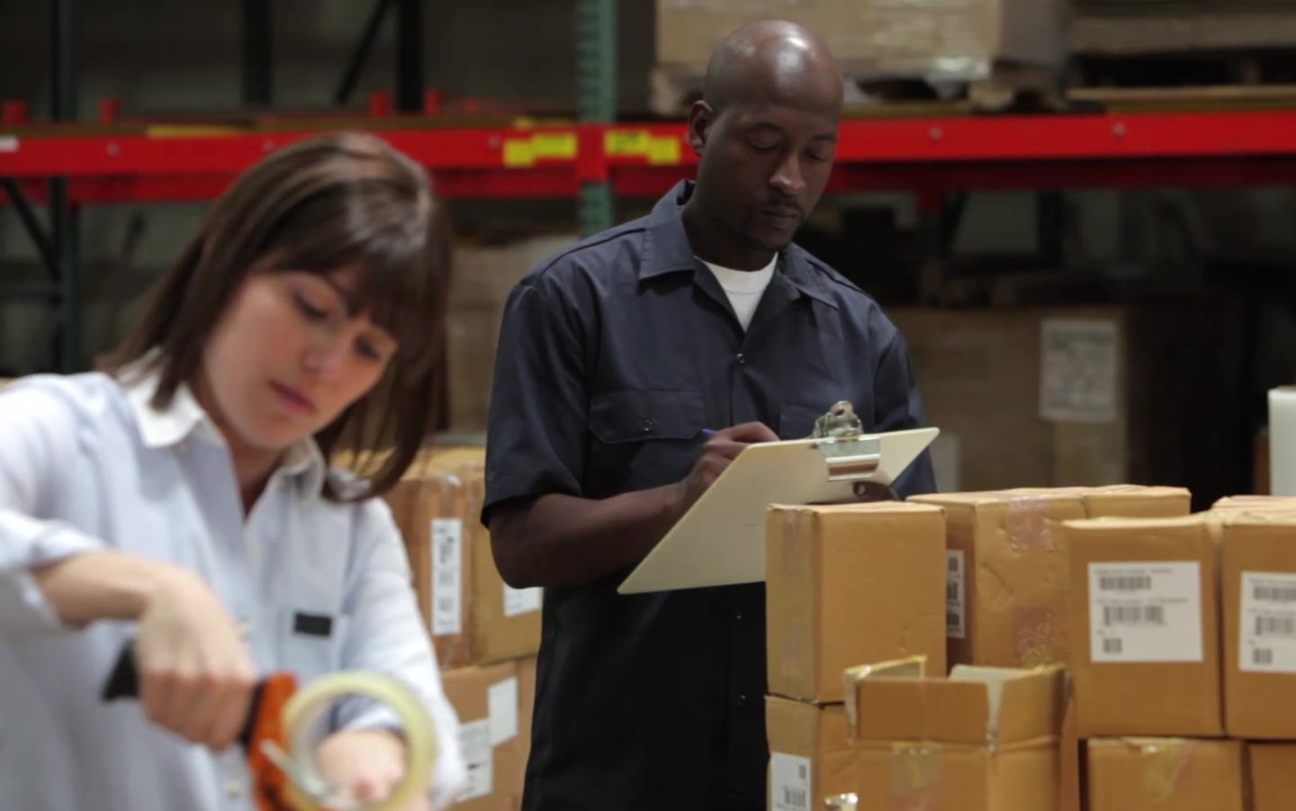 A man and a woman working in a warehouse.