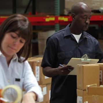 Man and a woman working in a warehouse.