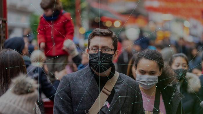 People wearing masks walking down the street.