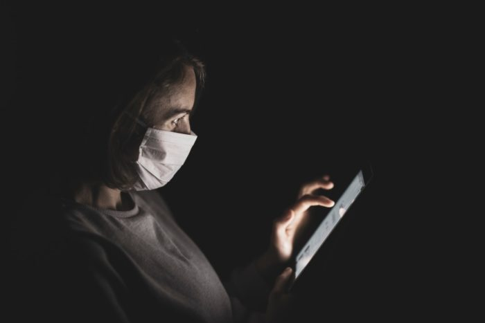 Woman wearing a mask working on her iPhone.