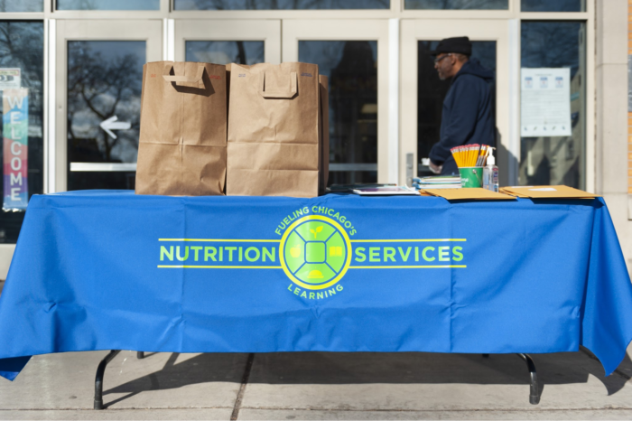 Volunteer table holding free lunches.