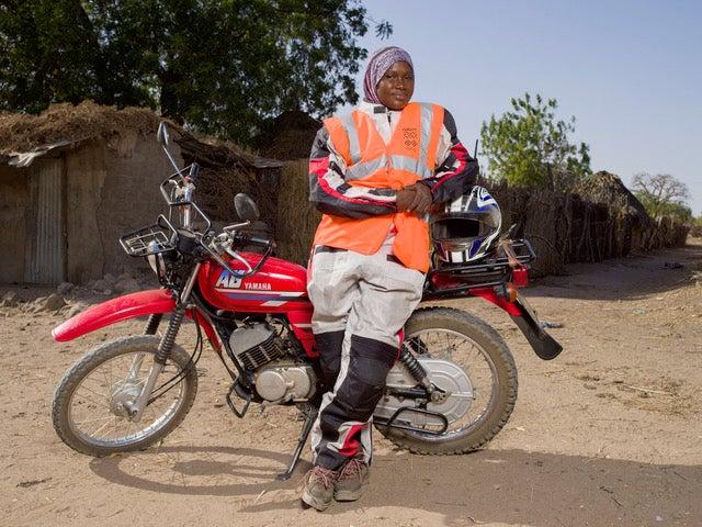 Volunteer leaning on a motorbike.