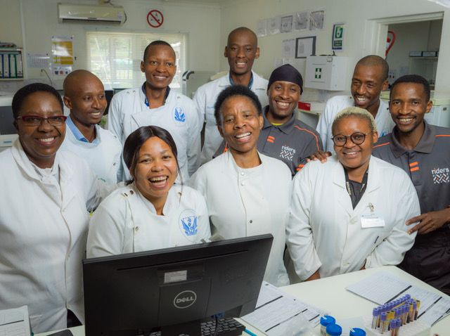Laboratory Staff and couriers for Riders for Health smiling.