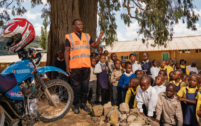 Riders for Health worker giving a presentation to a group of children..