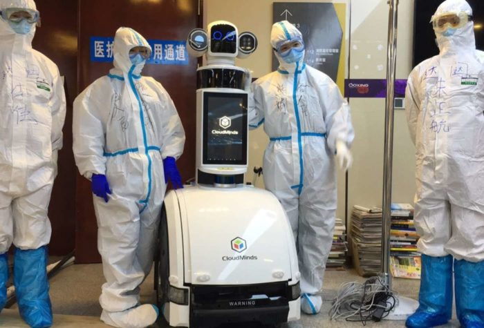 Healthcare workers in hazmat suits standing beside a robot designed to help them monitor Covid-19 patients.