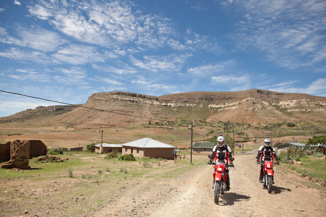Riders for Health workers riding motorbikes on a dirt road.