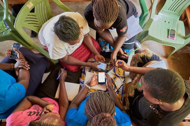 Group of women sitting in a circle holding mobile phones.