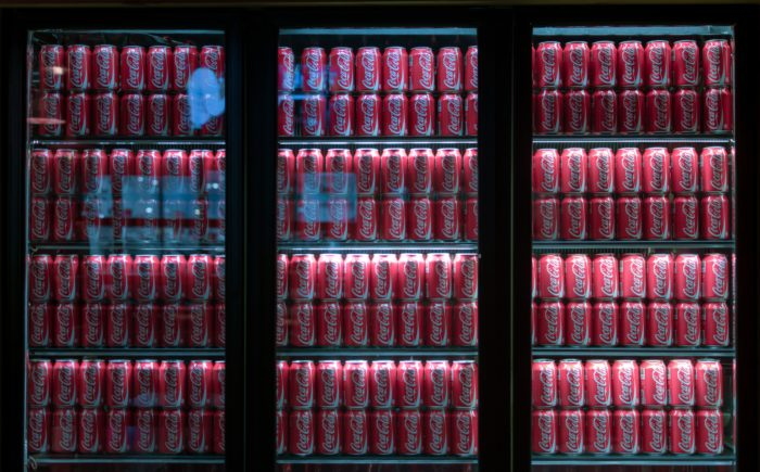 Fridges fully stocked with Coca-Cola.