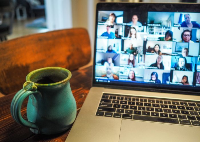 Coffee mug placed next to a laptop showing a video meeting.