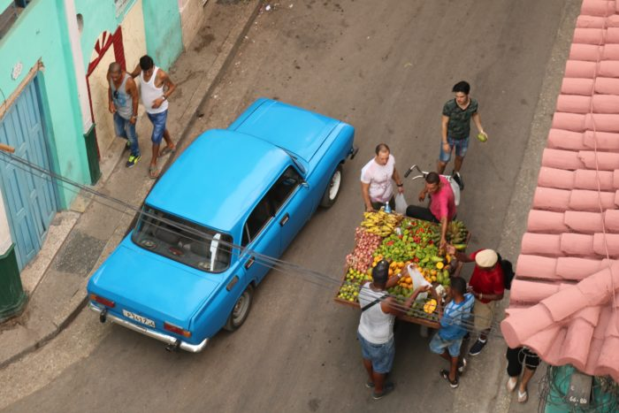 Car driving past a street vendor selling produce to people.