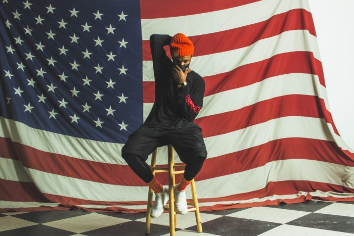 Judeus Samson sitting on a stool in front of a flag.