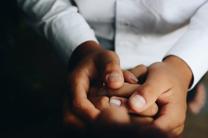 Two pairs of intertwined hands.