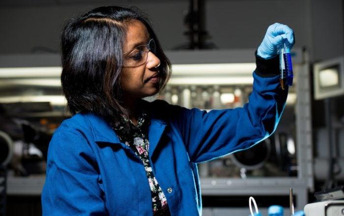 Female scientist holding two test tube beakers.