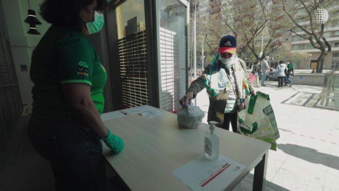 A man wearing a mask picking up food.