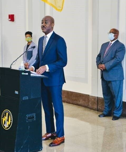 Otis Rolley giving a speech at a podium with two onlookers listening behind him.