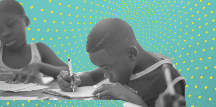 Two young children writing.