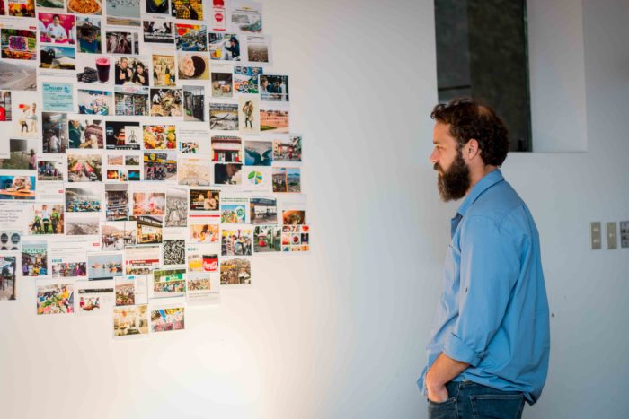 Man looking at a collage of photographs.