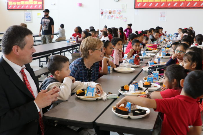 Michael Rosenberger, Urban School Food Alliance chairman, (left) and Katie Wilson, Urban School Food Alliance executive director, (right) join students for lunch at Felix G. Botello Elementary School in Dallas.