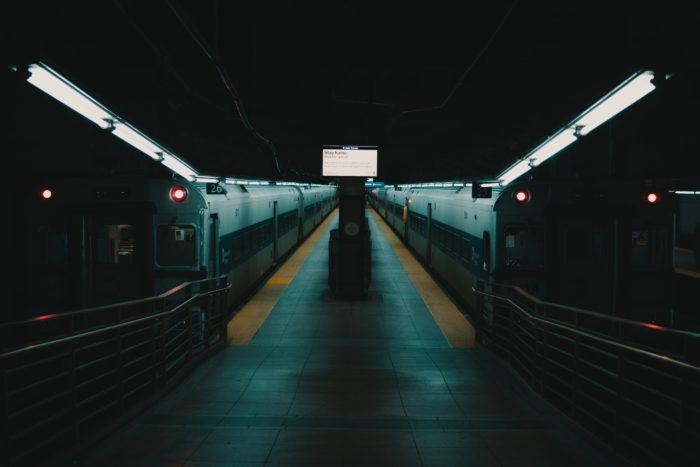 Two trains docked in an empty train station.