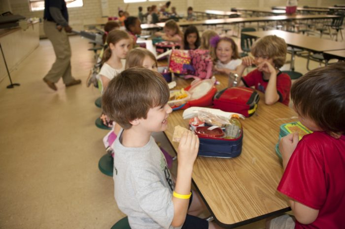 Group of students eating lunch at school.