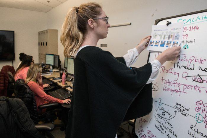 Woman attaching a sheet to a whiteboard.