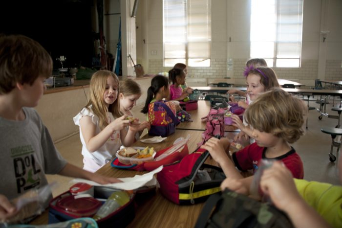 A group of children sitting at a table together eating lunch.