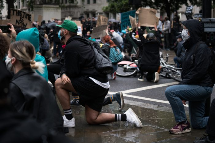 A group of protesters wearing masks kneeling on the street.