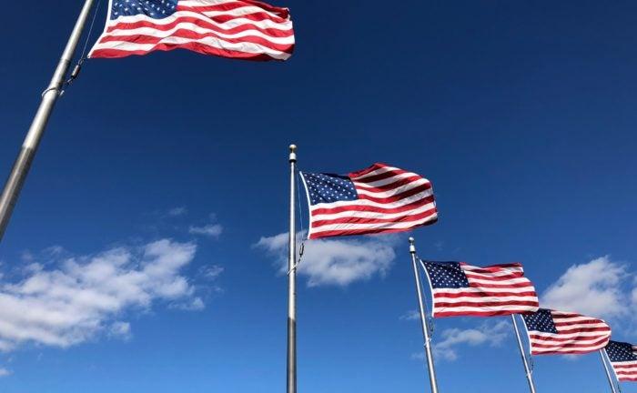 A row of flags under a blue sky.
