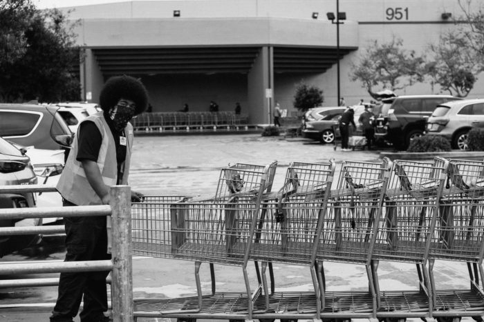 Store worker wearing a mask pushing shopping carts.