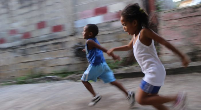 Two kids running through the street.