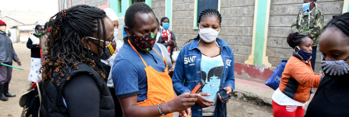 Volunteers wearing a mask showing an image displayed on his phone.