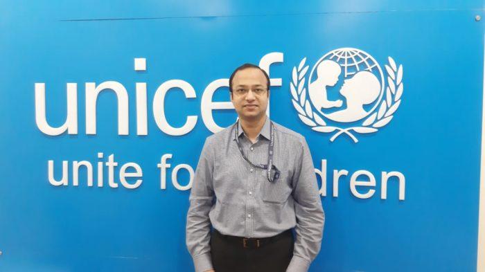 Dr. Sridhar Prahlad Ryavanki standing in front of a UNICEF sign.