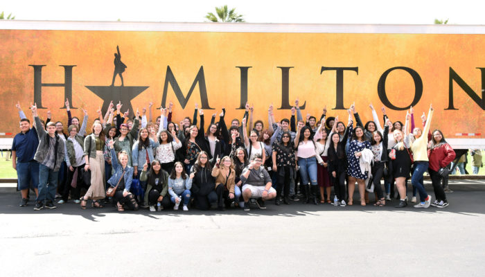 HEP participants gather for a photo in front of a Hamilton billboard.