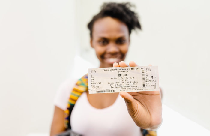 Woman holding a ticket to the Broadway show Hamilton.