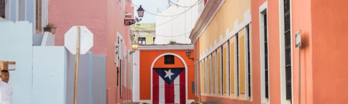 Colorfully painted street block leading to a wall with the flag of Puerto Rico painted on it.