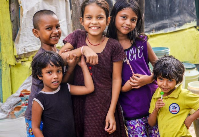 Smiling children in India waiting to get vaccinated.