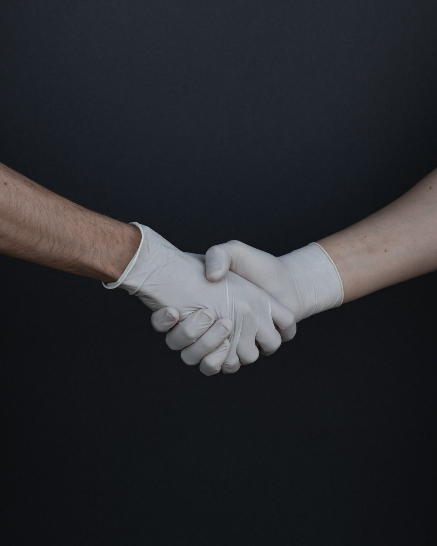 two hands shaking hands with medical gloves on