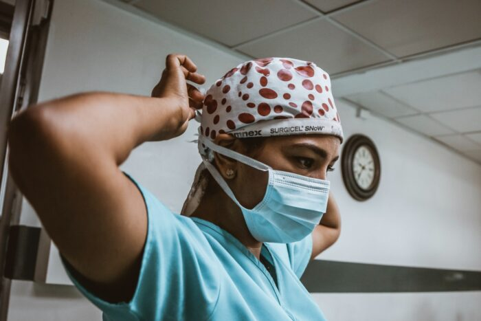 a nurse putting on PPE face mask