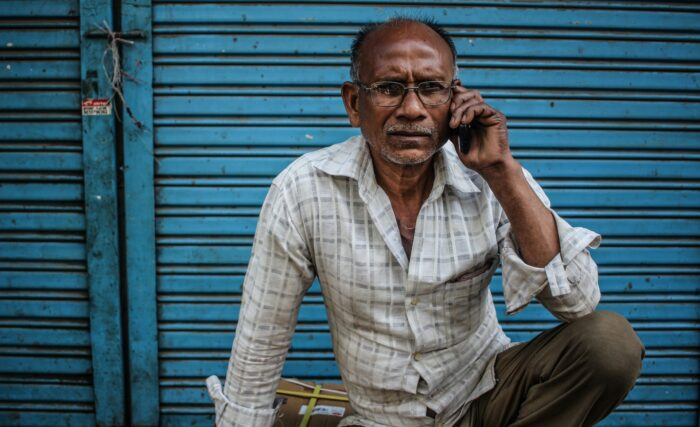 man in rural village on cell phone
