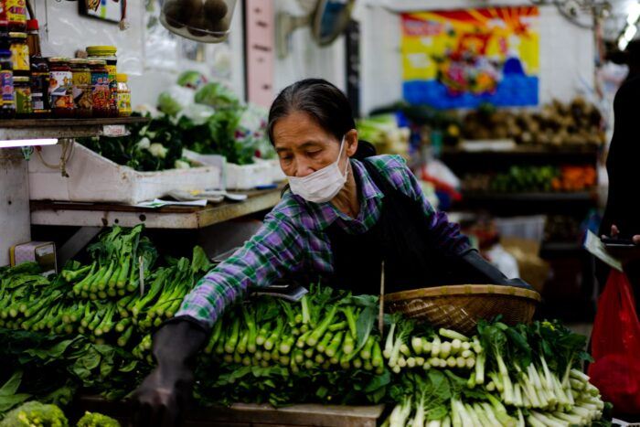 woman in asia market selecting vegetables with covid-19 face mask on