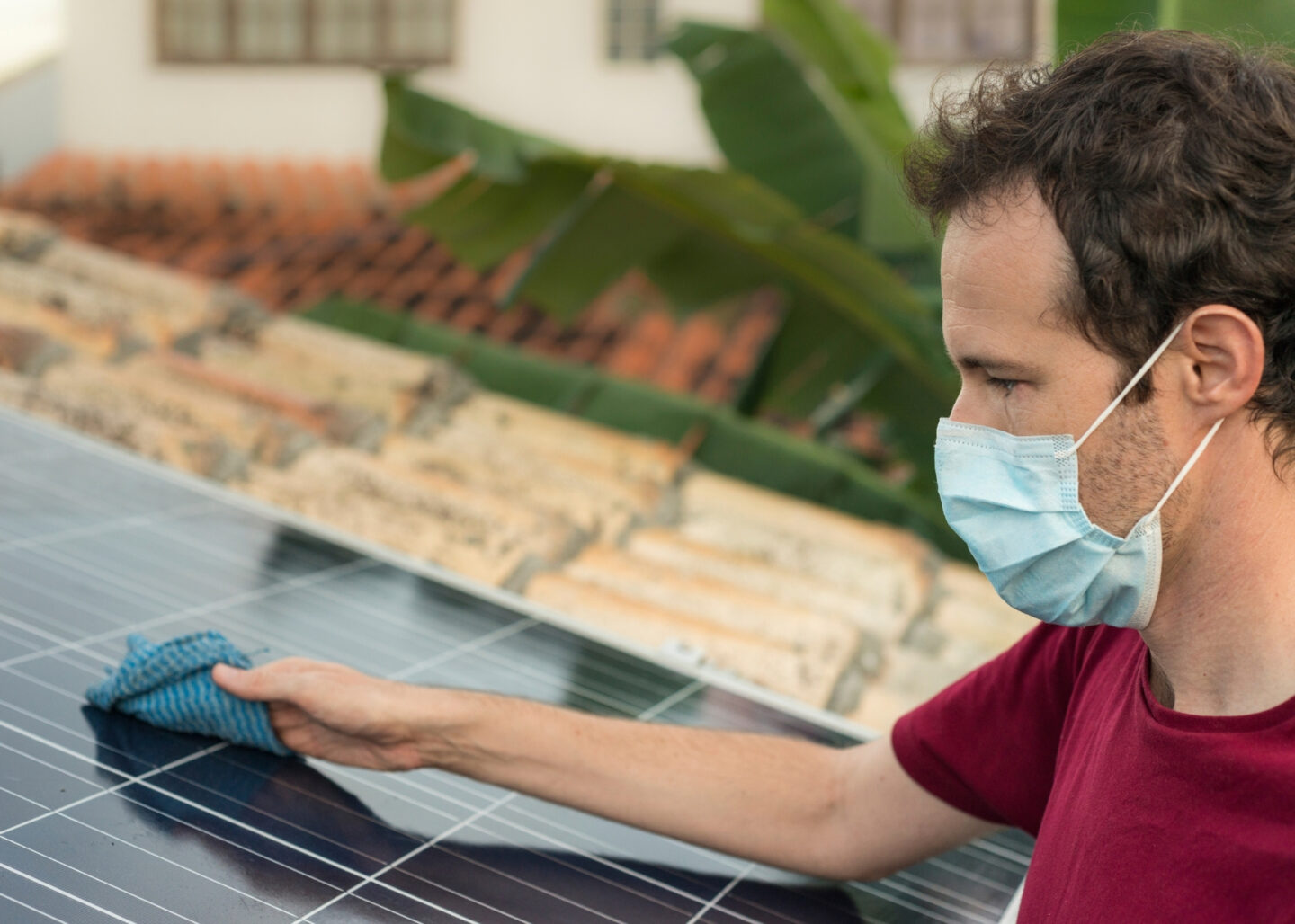 man wearing face mask cleaning solar power grid