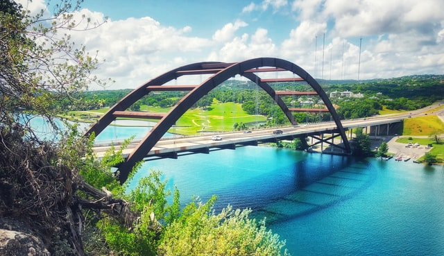 a bridge over a river with blue water