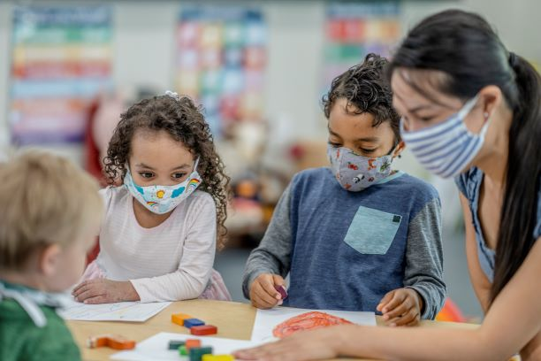group of young kids wearing masks around a table with teacher