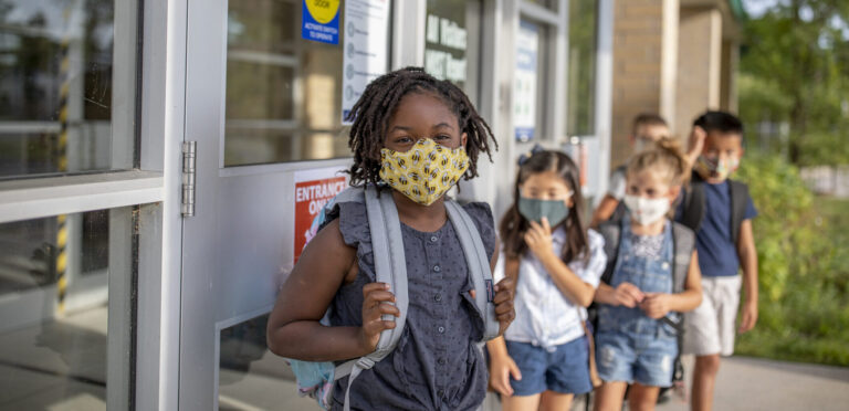 Image is of a diverse group of elementary school kids lined up outside of school wearing masks.