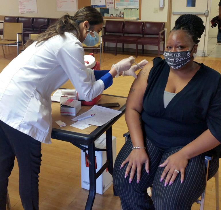 Image is of a woman sitting down getting a vaccine shot.