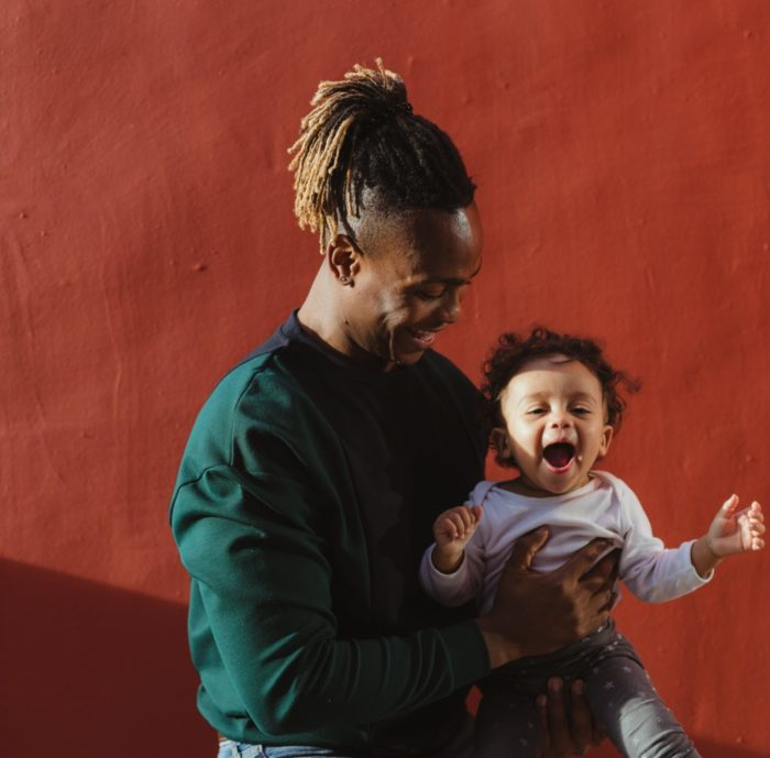 Humphrey Muleba holding his child.