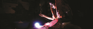 Woman sewing at night by a solar powered lamp.