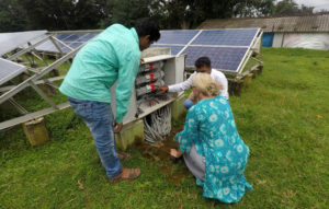 Workers examining a solar powered mini-grid.